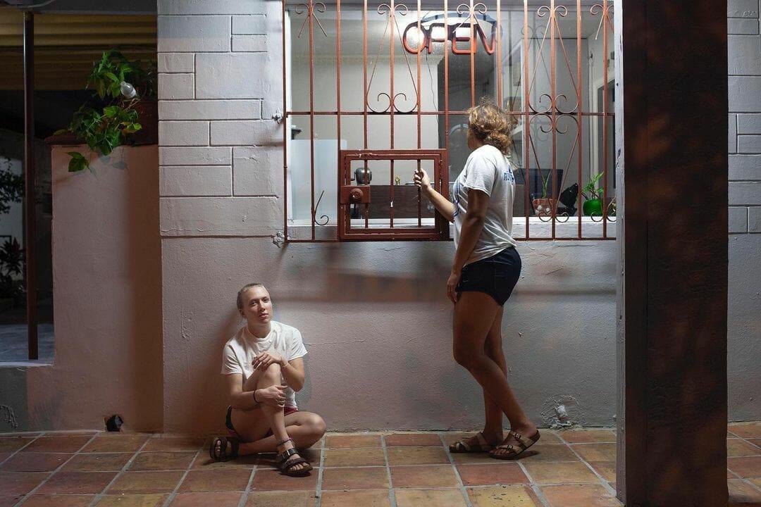 Des jeunes femmes sont dehors, devant la fenêtre d'un bâtiment. Elles sont éclairées par un néon blanc.