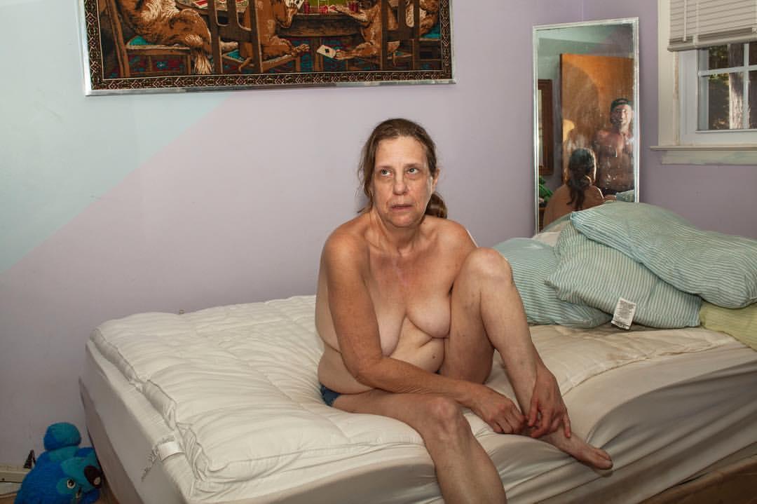 Une femme torse nue, ne portant qu'une culotte, est assise sur un matelas. Dans le miroir derrière elle on aperçoit un homme torse nu.
