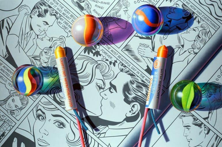 Nature morte typique de l'artiste Glennray Tutor : Sextet (Forever) - Peinture photoréaliste de quatre billes en verre et deux pétards posés sur des pages de comics romantiques (type Roy Lichtenstein). Jeu des couleurs des billes qui se reflètent sur le papier.