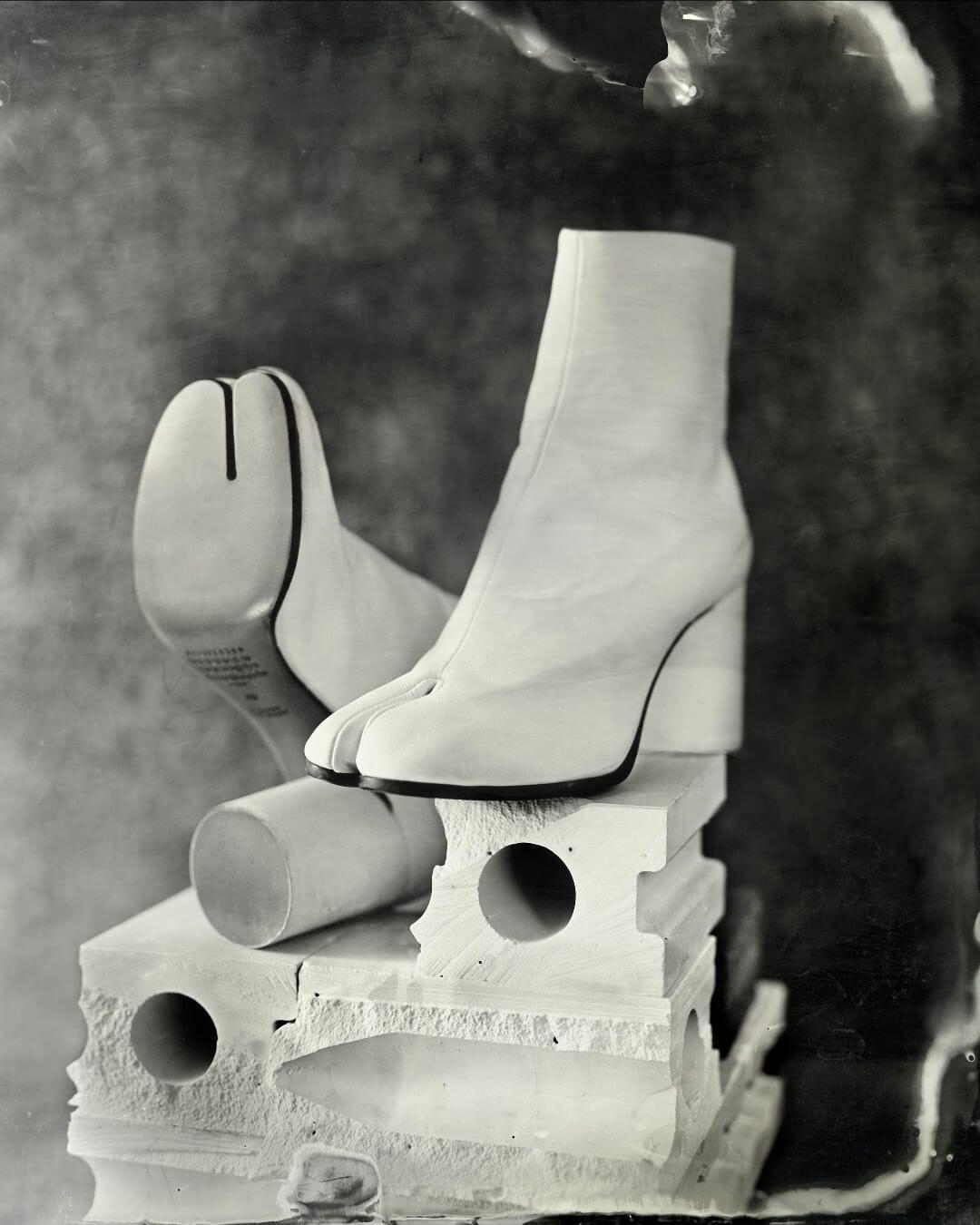 Bottines Tabi par Maison Margiela : bottine blanche à semelle noire, talon rond. À l'avant, au niveau des orteils, la chaussure est divisée en deux, presque comme une paire de tongues.