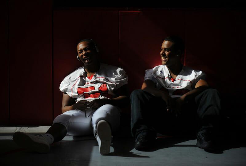 Deux jeunes hommes sont assis dans un vestiaire et rient ensemble, clair-obscur.