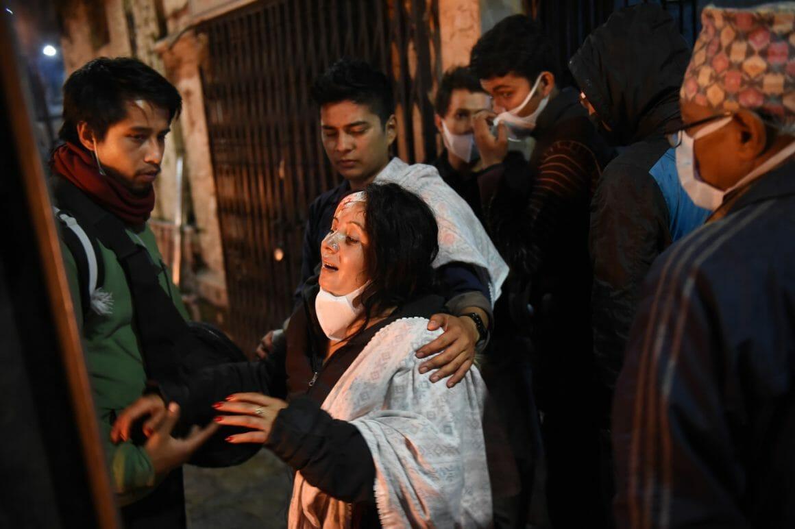 Une femme en larmes est entourée de plusieurs jeunes hommes qui la soutiennent.