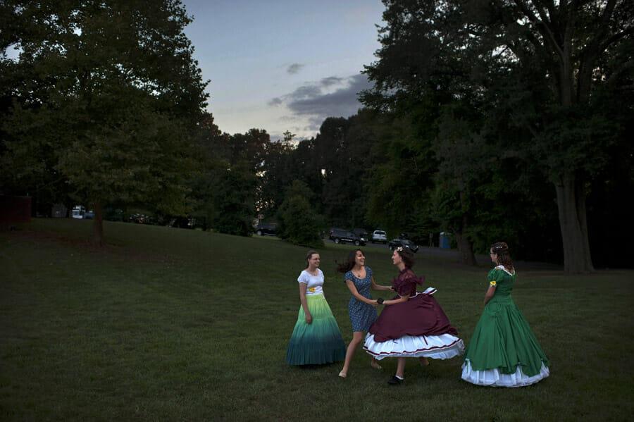 Des jeunes femmes rient, certaines en costumes d'époque d'autres en robe modernes dans une grande prairie. En fond un parking.