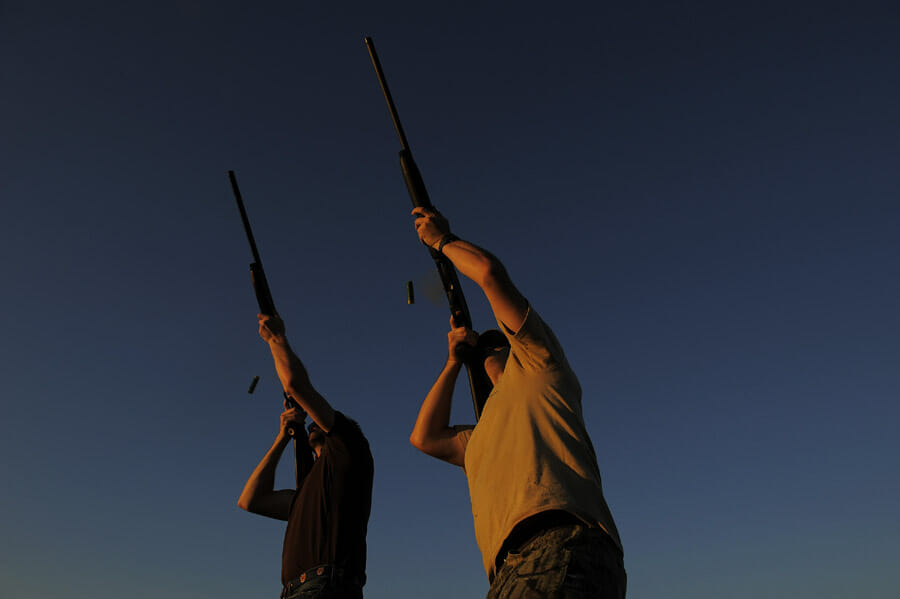 Deux hommes tirent à la carabine. Contre-plongée et lumière du soir.