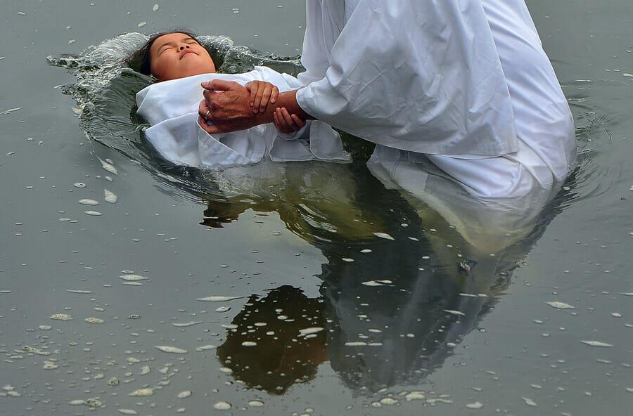 Une jeune fille est baptisée dans une rivière.