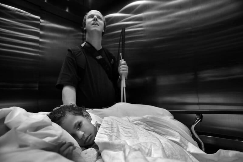 Le petit Panda, 6 ans est allongé dans un lit d'hôpital. Son père Jason lui caresse la tête d'une main, et tient sa cane d'aveugle de l'autre. Les deux sont dans un ascenseur en métal.