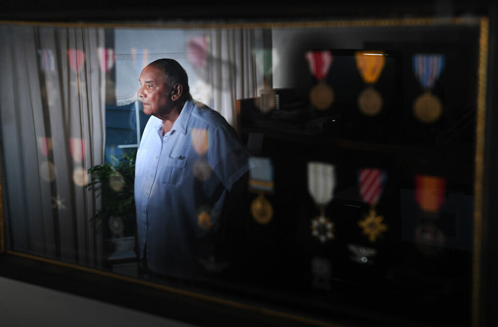 Portrait d'u homme chauve en chemise blanche, reflété sur le cadre où sont exposées ses médailles.