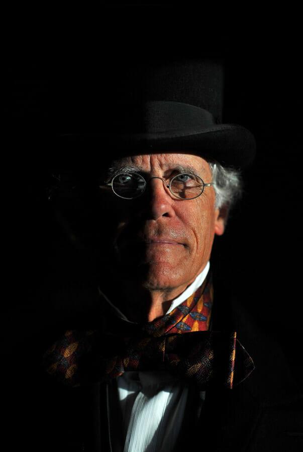 Un homme en costume d'époque, lunettes en demie-lune et écharpe aux couleurs chaudes. Clair-obscur.