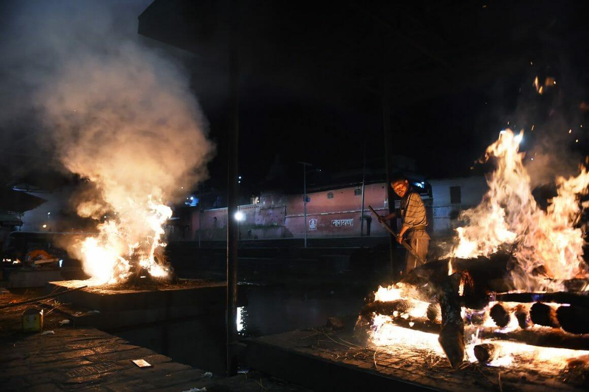 Un homme est entouré de deux feus funéraires.