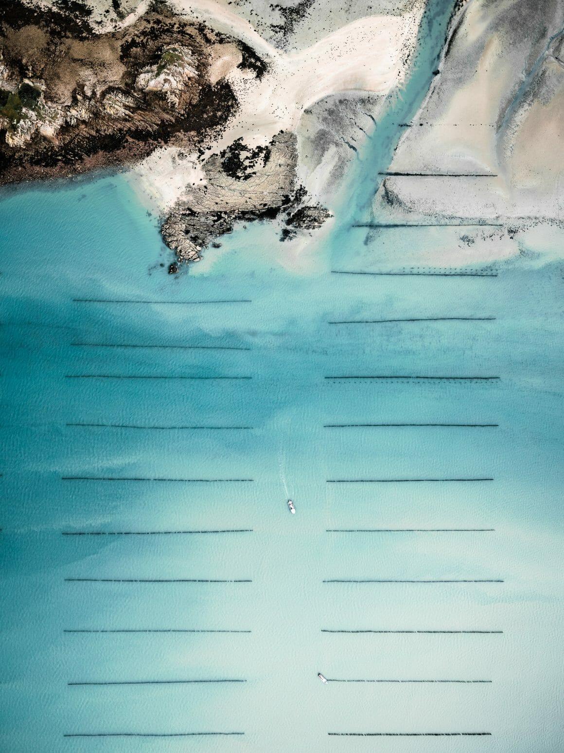 Lignes espacées d'ostréiculture, avec bras de mer donnant sur une plage sauvage. Jeu du blanc du sable, en contraste avec le bleu de la mer et la texture des pans arborés.