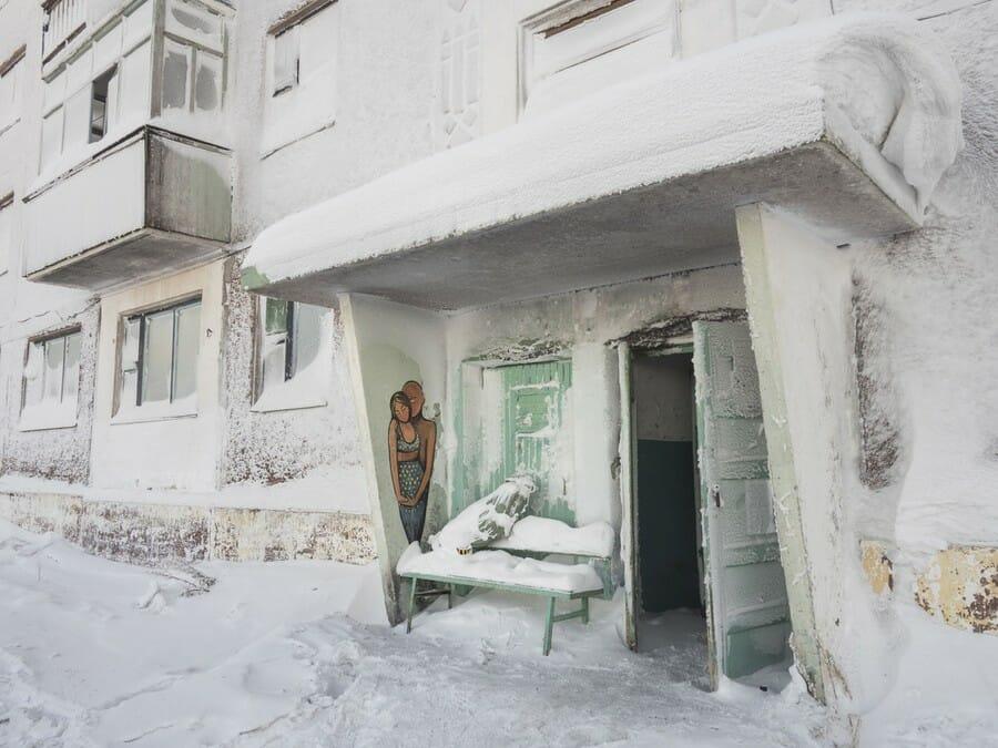 Une entrée d'un immeuble abandonné blanche de neige et de glace