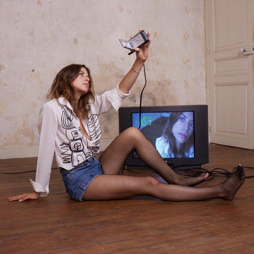 La chanteuse Alice et moi, assise sur le sol d'un appartement vide, se filme avec une caméra reliée à un écran, qui reflète son visage.