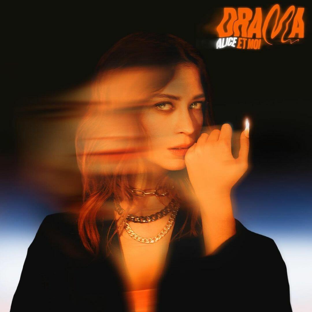 """Pochette de l'album """"Drama"""". La chanteuse s'essuie la bouche du dos de la main, de son ongle surgit une flamme. Couleurs chaudes et image déformée comme la lumière d'une bougie."""