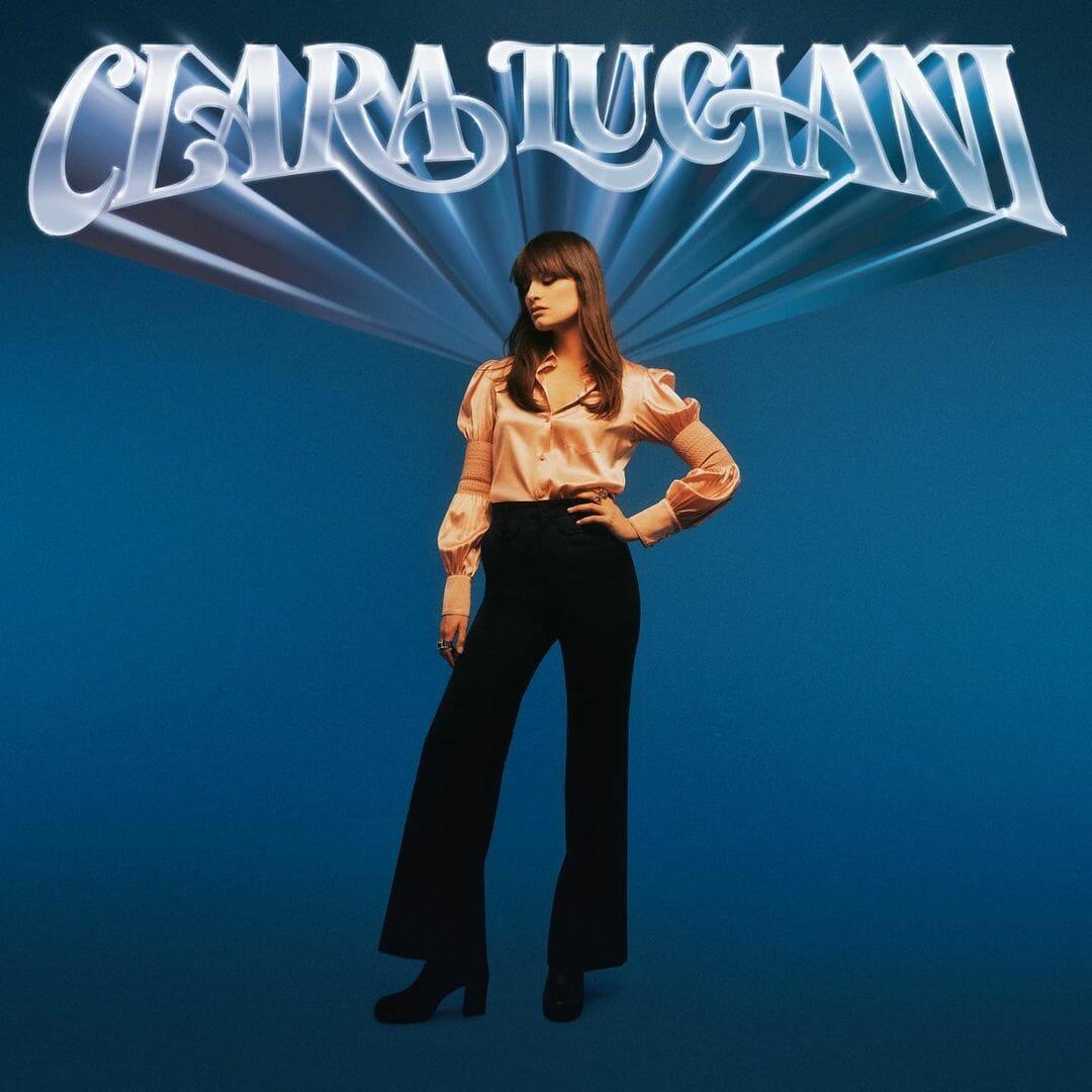 Pochette de l'album coeur, le nom de Clara Luciani est écrit en gros en haut sur un fond monochrome bleu. La chanteuse s'y distingue, en posant la main sur la hache et le regard baissé.