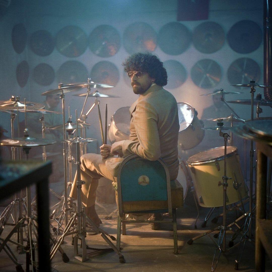 Le musicien se tient assis, dos à nous mais tourné vers la caméra, devant un drum set au coeur d'une pièce recouverte de cymbales.  Gaspard Augé Force majeur