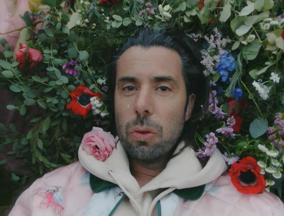 Le chanteur pose, la tête sur un oreiller de fleur, et une larme coule sur sa joue.