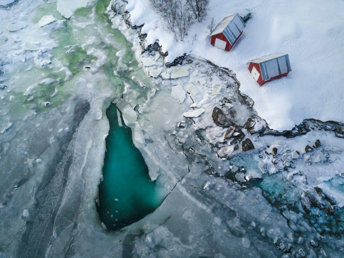 Plan sur un lac gelé vu du ciel. Tout est recouvert d'une neige épaisse, sauf un pan de lac très bleu, presque vert.