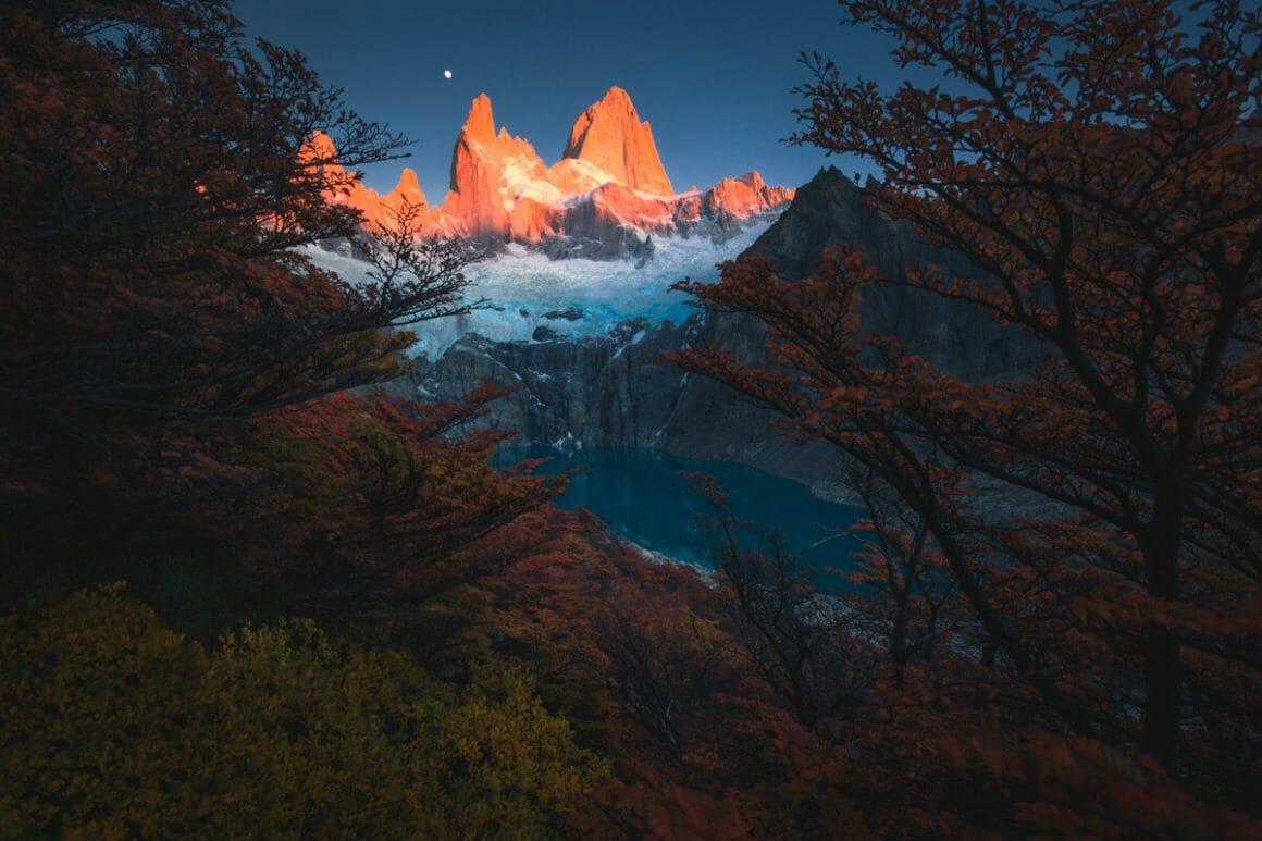 Plan en plongée, depuis un espace arborée et orangé. Un lac bleu se distingue, au creux d'une montagne grise, touchée par les derniers rayons de soleil rose.