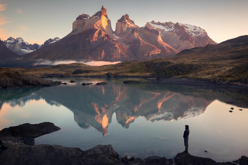 Plan sur un lac, où se reflète des montagnes brunes baignées dans une lumière chaude.