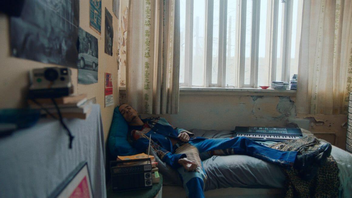 Homme endormi, sur un lit. Un clavier de piano est posé à côté de lui, dans une chambre rétro et délabrée.