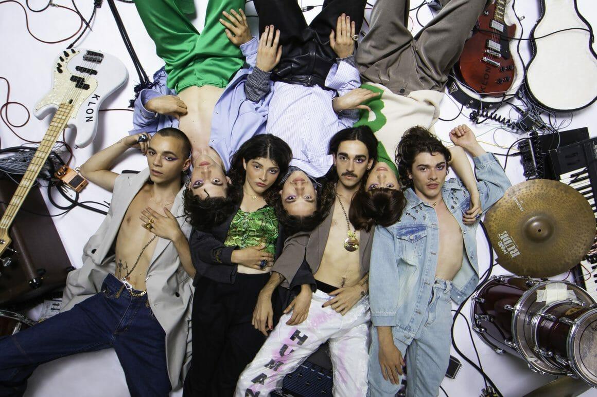 Les membres du groupe sont allongés au sol, au milieu de leurs instruments. Cotes à cotes, leurs têtes se touchent.