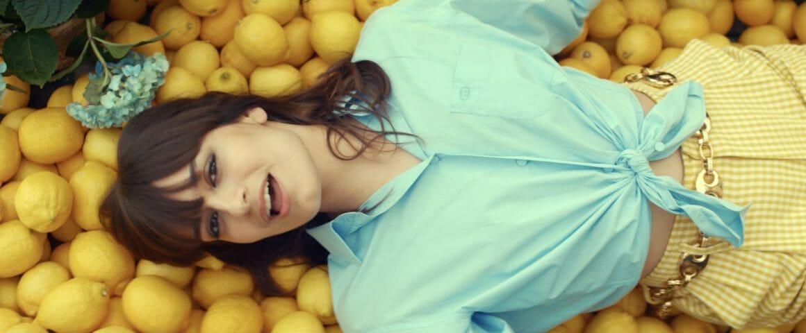 La chanteuse est allongé sur un lit de citrons, qui reprend les couleurs de son pantalon. Elle chante en regardant la caméra, qui la filme en plongé.