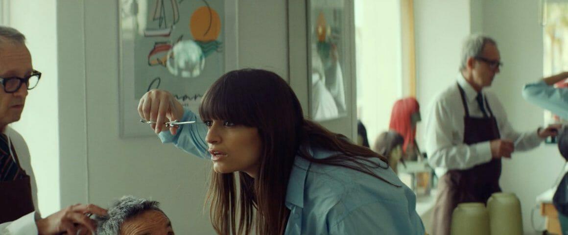 Clara Luciani retouche sa frange signature dans un salon de coiffure vintage, pendant qu'un coiffeur la regarde.