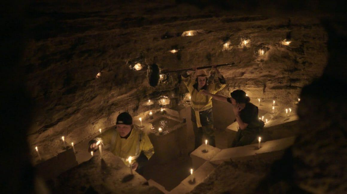 Dans une grotte, Myd tient la perche au dessus d'un point d'eau, pendant que le second personnage lui indique le geste qu'il doit faire et que le troisième allume des bougies.