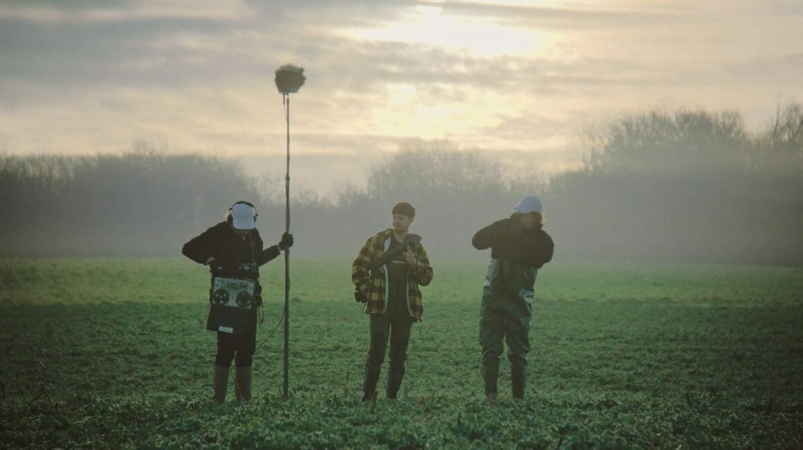 Les trois personnages se préparent à enregistrer les sons de la nature, dans un champs au petit matin.