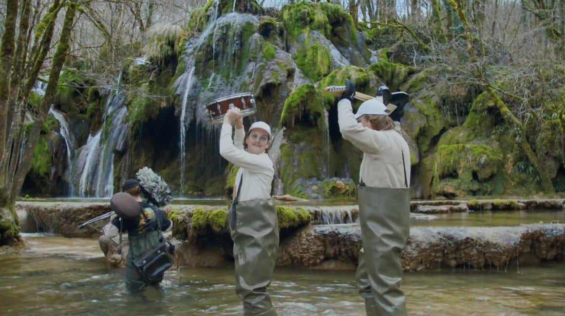 Les trois personnages traversent une rivière, en tenant leurs instruments au dessus de leurs têtes , paysage sauvage.