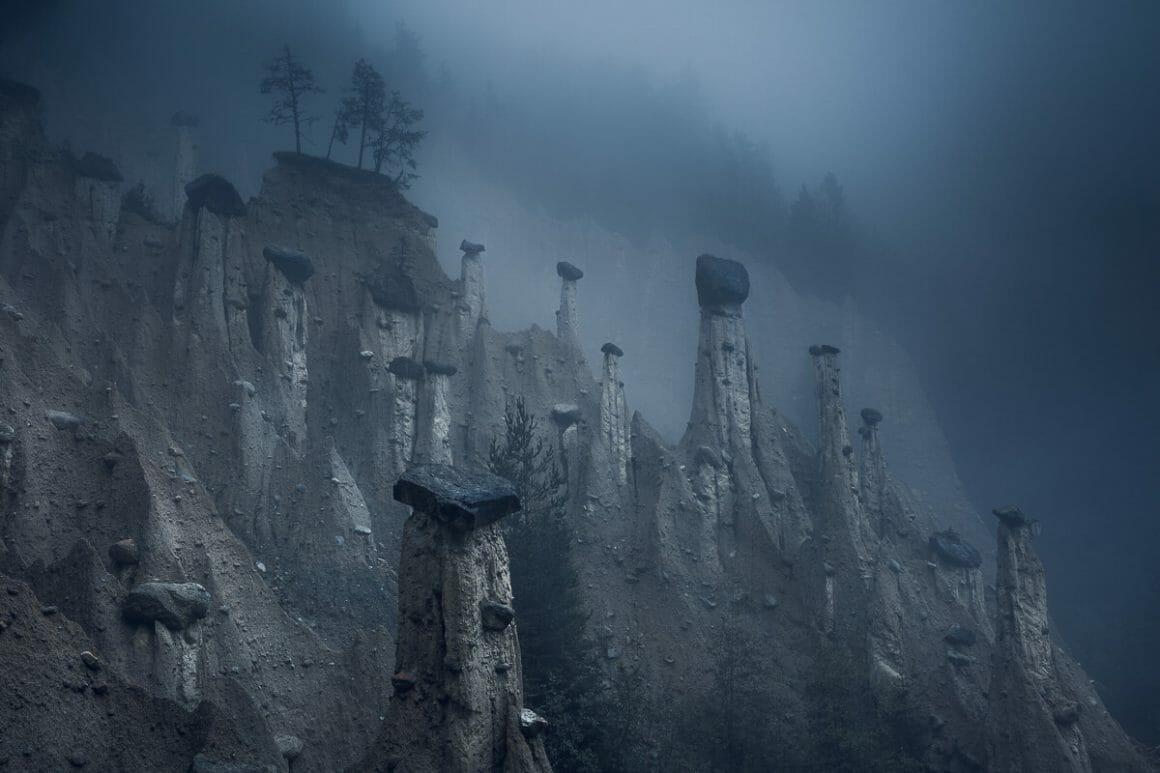 Bord de montagne, brouillard noir. Le sol a été comme mangé, laissant des pics abrupts se distinguer, avec des pierres noires à leur sommet.