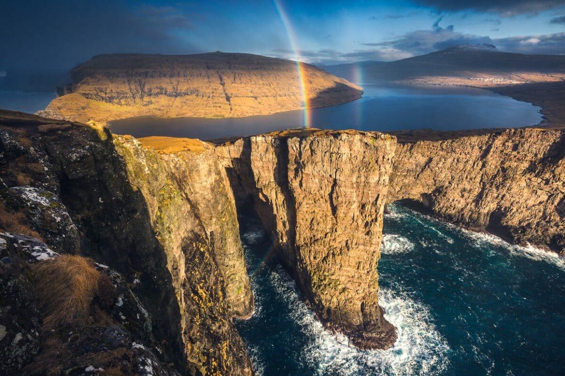 Plan large, falaises brun clair et mer bleue en premier plan, grand lac bleu et reliefs ocre plus loin. Entre les deux, un arc en ciel fait le lien.