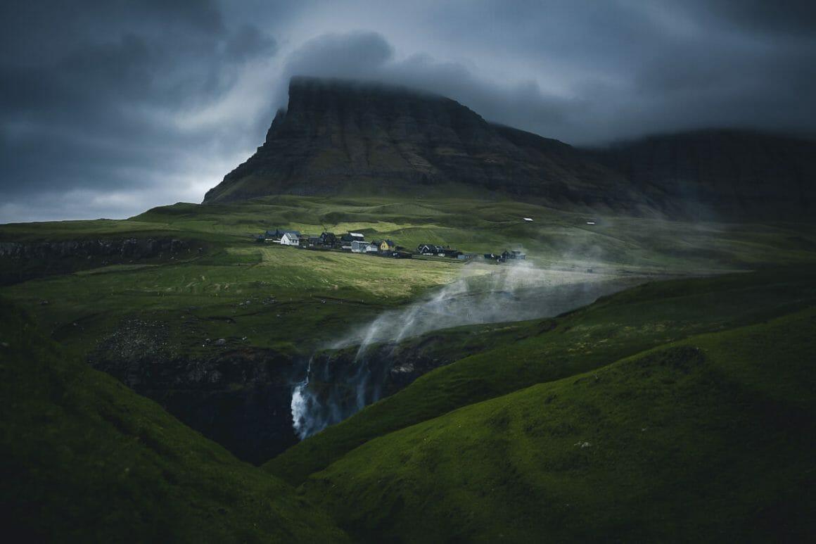 Grandes prairies verdoyantes, un village au loin, avant un massif rocheux. Lumière sombre et nuages bas.