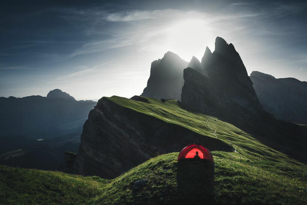 Toujours la même tente rouge, sur une prairie verdoyante, en bord de montagne. Reliefs montagneux qui font un jeu de lumière.