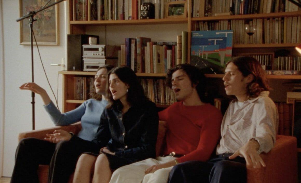 Plan sur les quatre choristes, assis sur un canapé devant une grande bibliothèque. Deux filles à droite, deux garçons à gauche, chantent le refrain en se concentrant.
