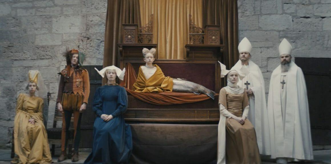 """Plan de la """"reine"""", entourée de sa cour. A sa gauche, deux évêques et une religieuse, à sa gauche deux dames de compagnie et un bouffon. La reine est allongée et possède une queue de poisson."""