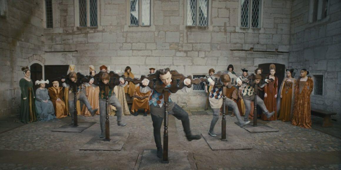 Plan de Tommy Cash et ses comparses, habillés en bouffon, attachés à des piloris qui dansent pour amuser une cour dans un château.
