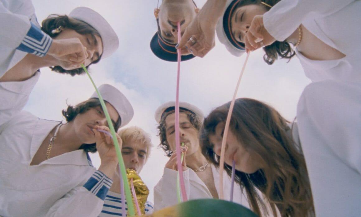 Plan en contre-plongée. Tous les membres sont penchés sur un bol, d'où ils boivent avec des grandes pailles, déguisés en matelots.