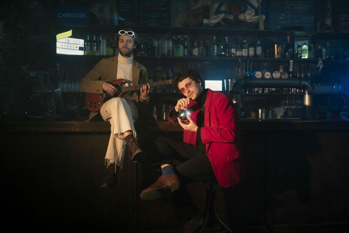 """Dans un bar sombre tiré du clip """"Dehors"""", Ludovic Bailly à droite est assis sur le comptoir, sa guitare sur les genoux. A gauche, Emmanuel Jarrige sirote un cocktail dans une mini boule à facette, accoudé au comptoir."""