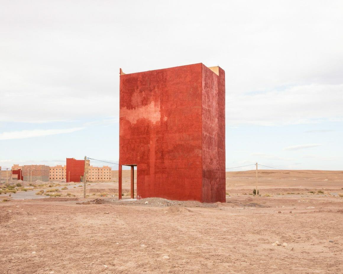 Photographie d'une structure inconnu au milieu du désert, en fond d'autres structures