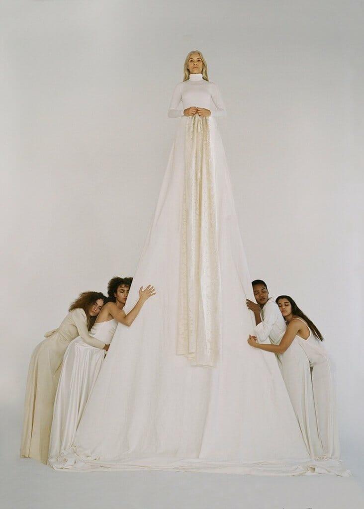 femme âgée avec une très longue robe blanche entourée de 4 femmes qui l'enlacent