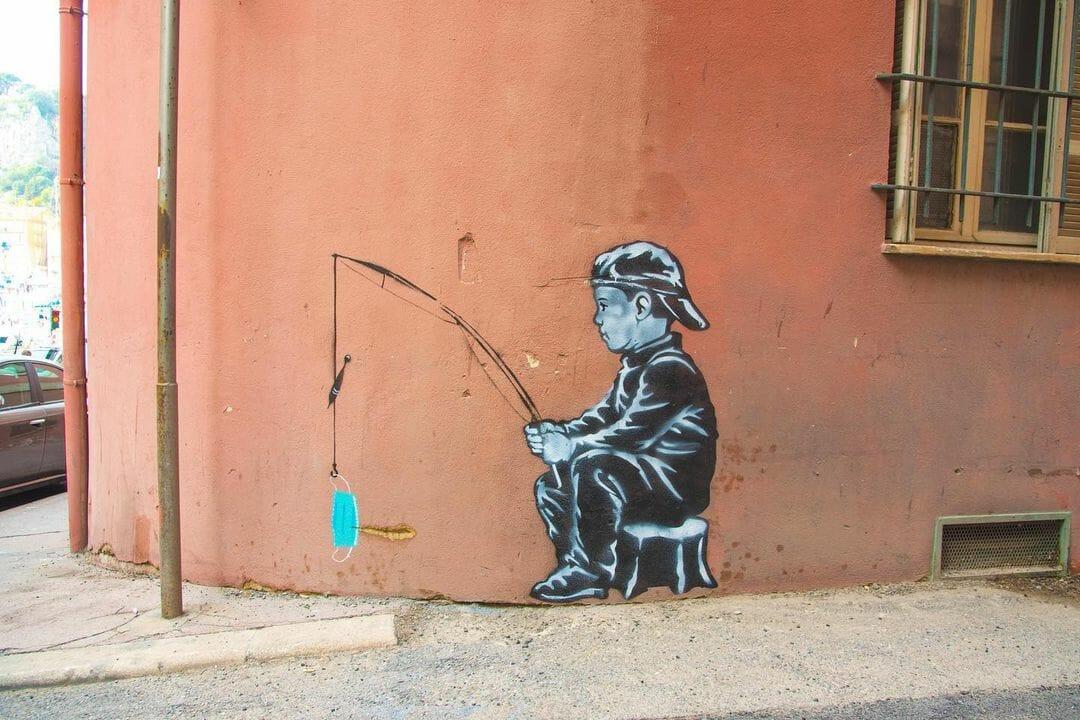 Peinture en noir et blanc au mur. Petit garçon qui tient une cane à pêche dans ses mains. En couleur, au bout du fil, un masque chirurgical.