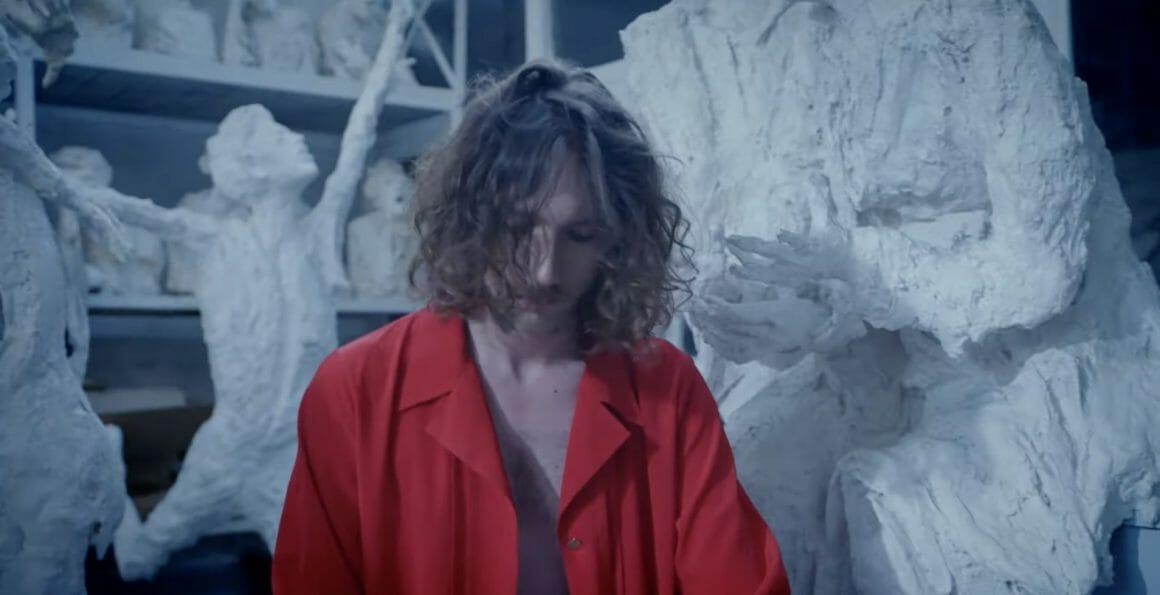 Alexandre Laudou, la tête penchée sur son clavier (hors champs). Il porte une chemise rouge ouverte, qui contraste avec les statues en plâtre derrière lui. Les mains d'une des statues sont ouvertes vers le ciel, touchant presque ses cheveux.