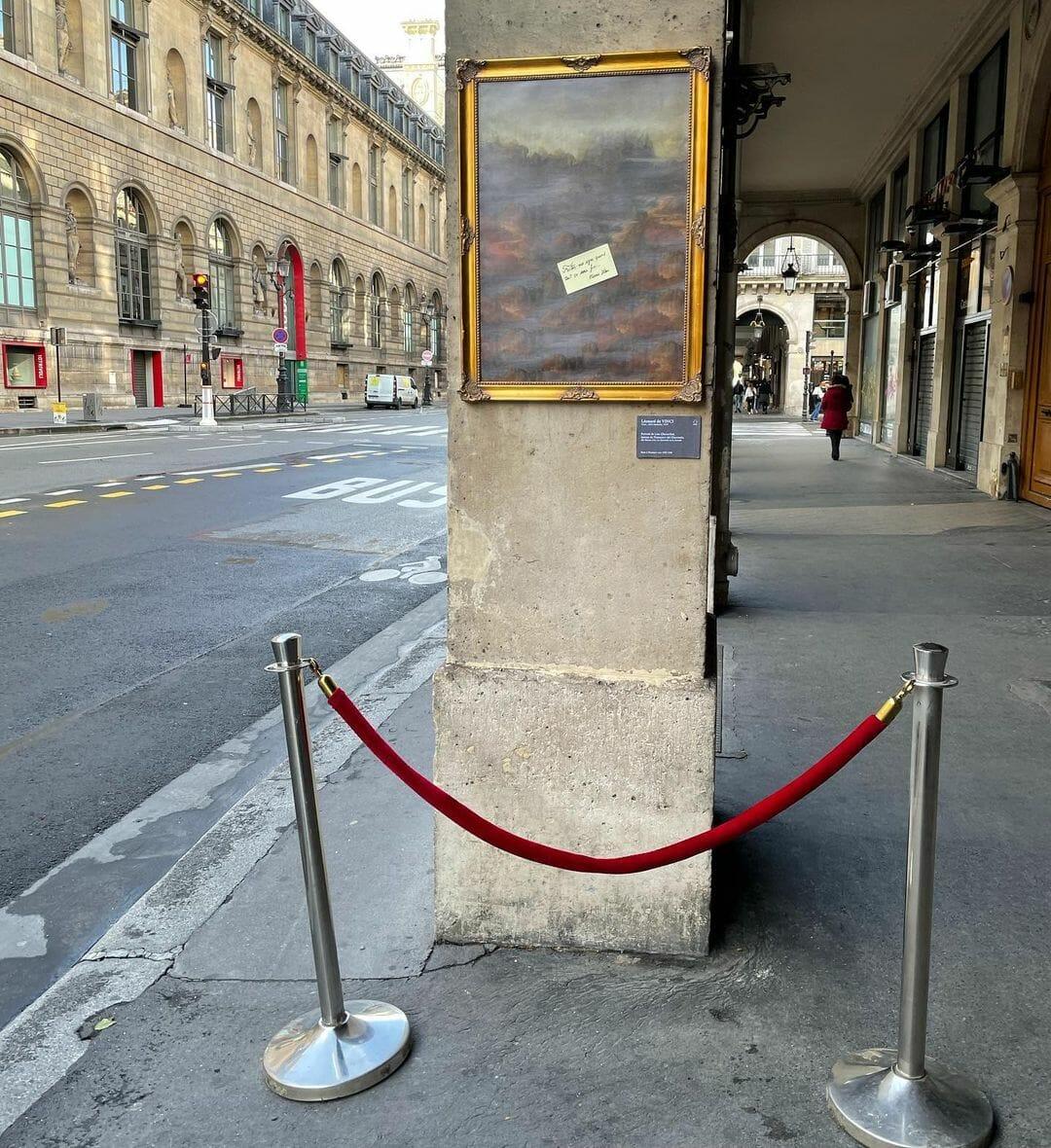 En face du louvre, sous les arcades : toile encadrée au mur, La Joconde sans Mona Lisa. En biais, au milieu, un post-it jaune.