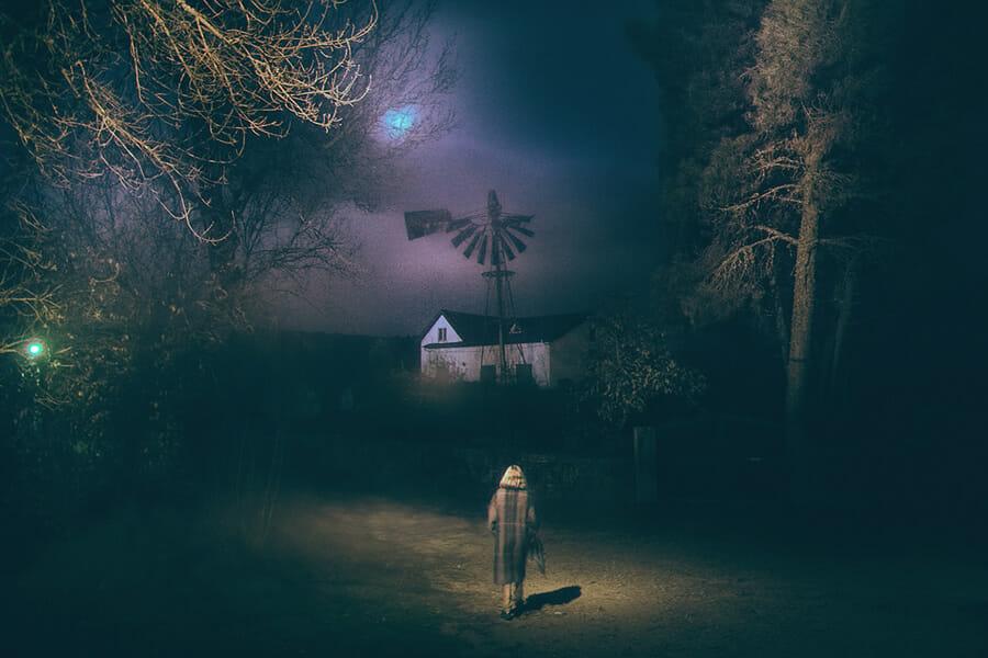 Sur cette oeuvre d'Henri Prestes, on peut voir une femme en premier plan de dos, marchant vers une maison dans la nuit
