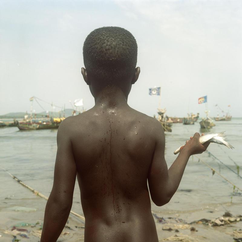 Photographie d'un enfant ghanéen de dos tenant un poisson.