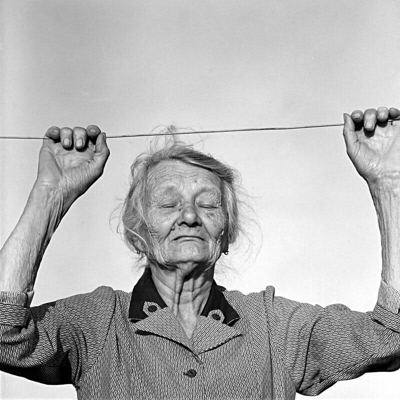 Photographie d'une vieille femme qui se tend à une corde à linge.