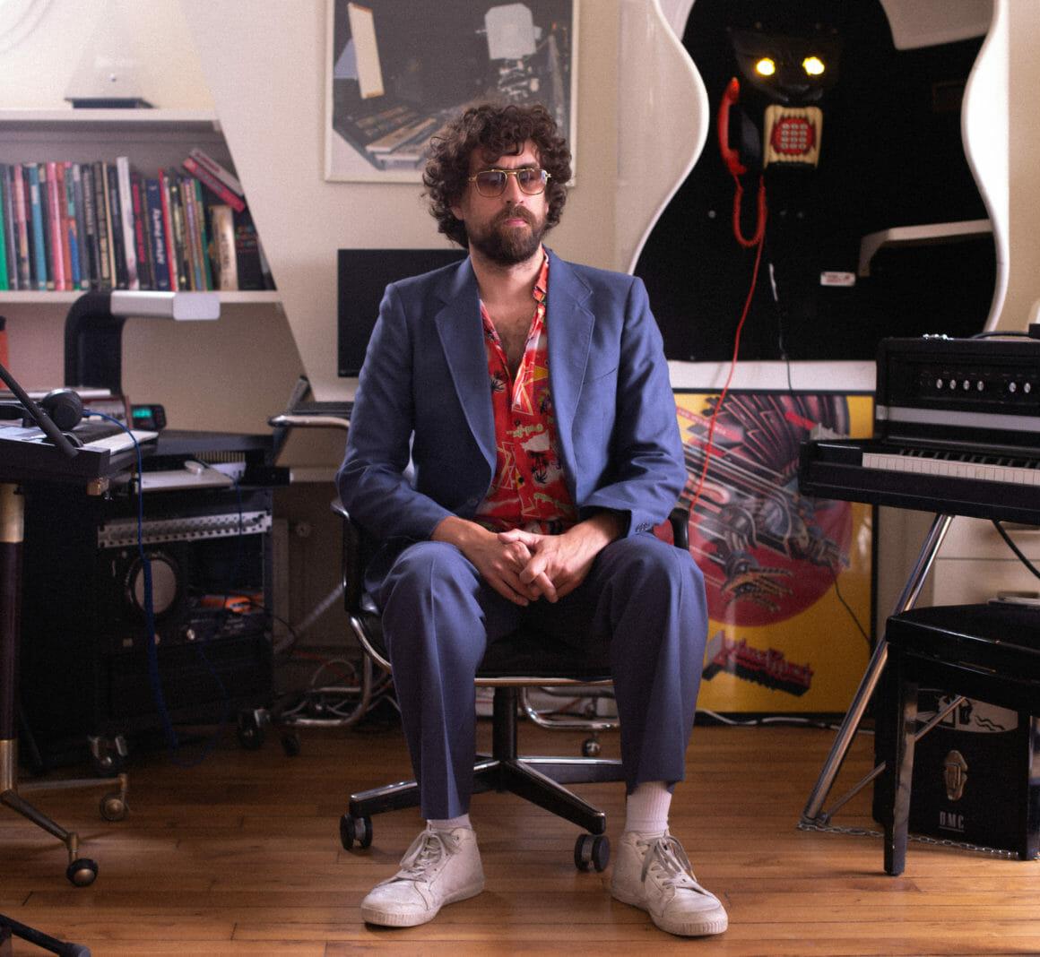 Gaspard Augé, vêtu d'un costume bleu et d'une chemise hawaïenne nous reçoit dans son studio pour nous parler de son album Escapades.