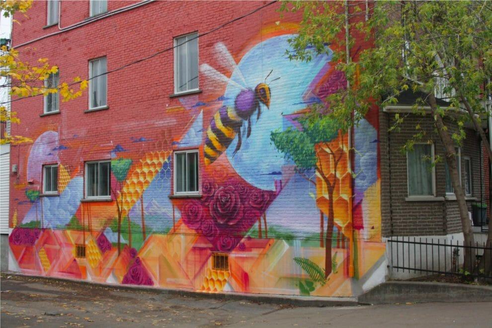 Oeuvre de l'artiste sur un bâtiment en brique représentant le cycle de la pollinisation d'une abeille