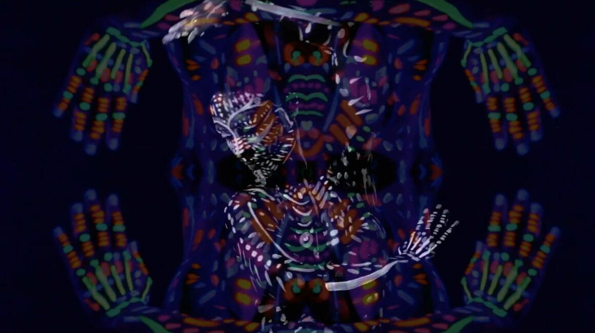 Au premier plan, les mains de la danseuses forment un cadre autour de celle qui danse, au centre perdue dans le mouvement.